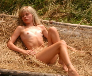 Young kirmess reveals her tan lined body atop a wagon brim encircling straw
