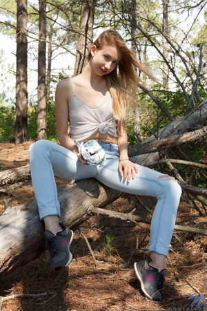 Teen girl Dominica slips off faded jeans to show her bald twat in the woods