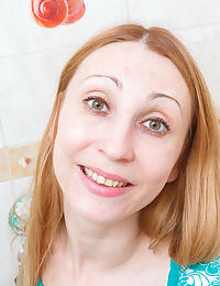Mature blond with hairy kitty poses on cam in the bath stretching pussy lips