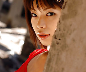Stunning asian coed Hikari Hino poses wearing only a sheer red dress