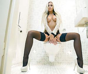 Blonde in black lingerie is stroking her vagina in the bathroom