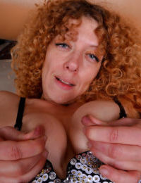 Older redhead Leona spreading hairy pink pussy after slipping thong off ass